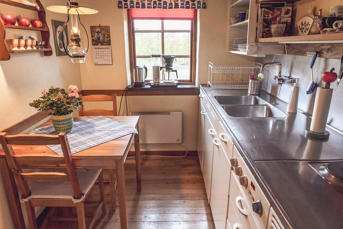 Köket i stora gårdslägenheten vetter mot äppelodlingen och är fullt utrustat för självhushåll.